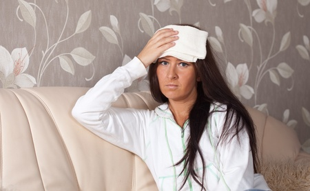 Suffering woman stupes  towel to her head