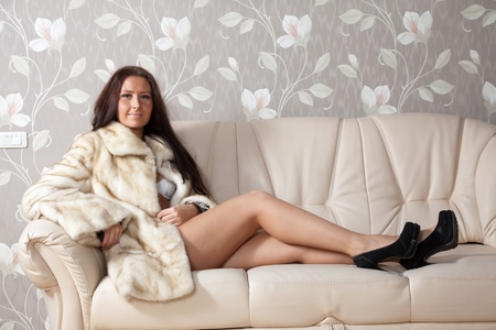 sexy fur: woman in a fur coat sitting on the couch at home Stock Photo