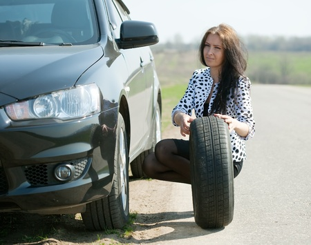 flat tyre: Woman changing car wheel at road