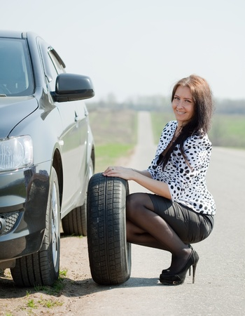 woman during the wheel changing at road Stock Photo - 13306072