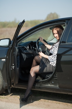 middle age woman get out the car and looking at camera Stock Photo
