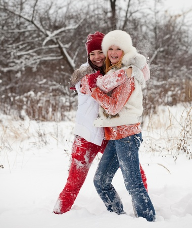Happy girls plays with snow at winter park photo