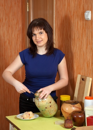 Woman with can of pickled cabbage at her kitchen Stock Photo - 13393845