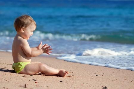 klein meisje op strand: Gelukkig peuter zit op strand