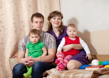 Family of four on sofa at home Stock Photo - 13394894