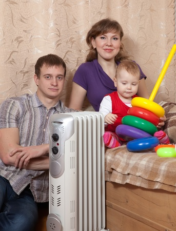 heat register: parents and child  near warm radiator  in home Stock Photo