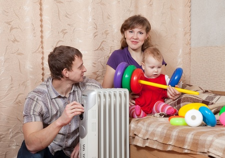 and heating: Family  relaxing at home near oil heater