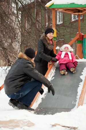 happy parents with  toddler on slide playground area in winter photo