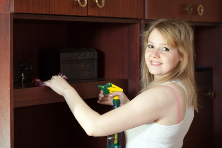 Happy  girl cleans furniture at home  photo