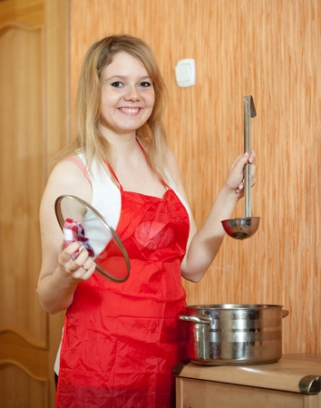 Happy woman with  saucepan at her kitchen photo