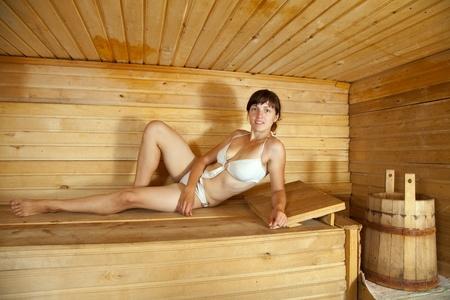 sauna nackt: Mädchen liegt auf Holzbank in Sauna