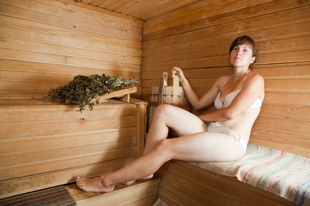 Young woman  sitting on wooden bench  at sauna   photo