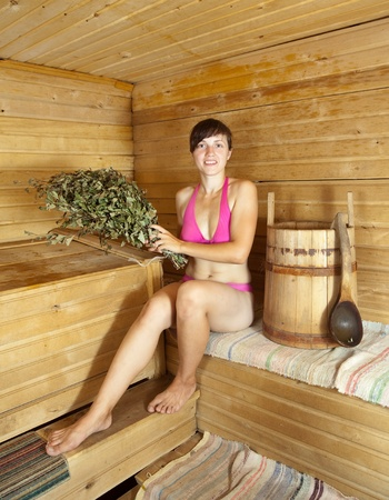 girl is steamed in the sauna with birch twigs Stock Photo - 13453799