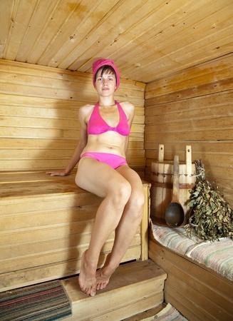 Young woman take steam bath in sauna photo