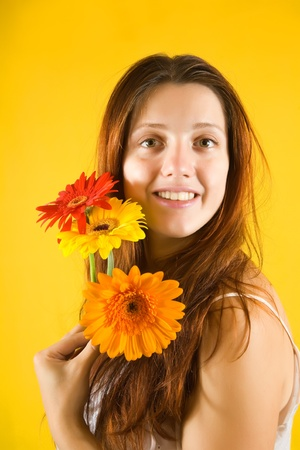 glamour portrait of pretty girl with  flowers over yellow background photo
