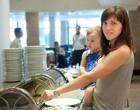 Woman with child gathers food at the buffet photo