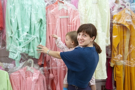 Happy mother and daughter chooses clothes at shop photo