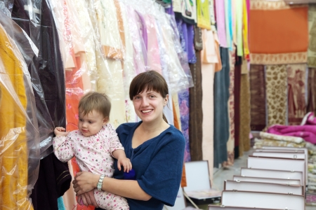 Happy woman and child chooses clothes at shop photo