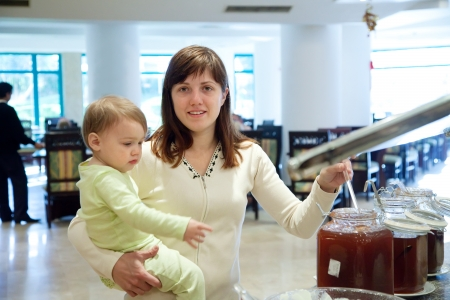 Mother with child takes jam on the buffet table photo