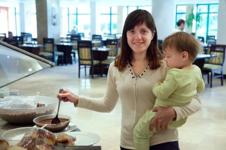 Woman with child takes chocolate cereals on the buffet table photo