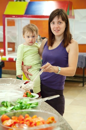 Woman with chid chooses  fresh vegetables  in buffet at hotel photo