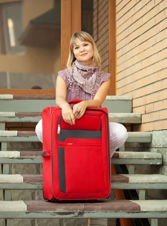 woman with baggage sittng near home door photo