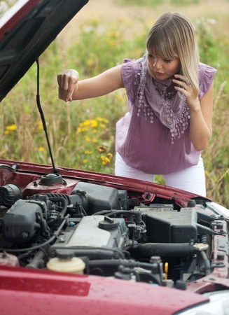young woman with her broken car in summer day photo