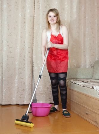 woman washes the floor with mop in the living room Stock Photo - 13453785