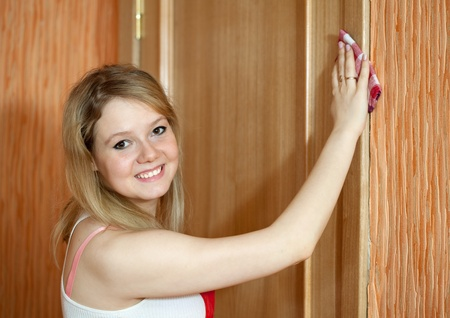 Happy girl wipes the dust from the furniture at home Stock Photo - 13453732