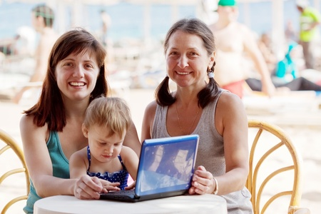 happy women and  girl   with laptop   at resort hotel area photo