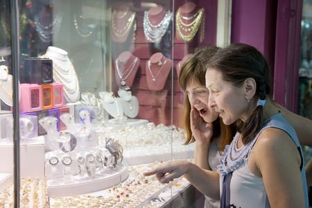 Two women looking jewelry counter at shop photo