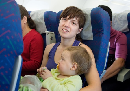Mother and child traveling on commercial airliner photo