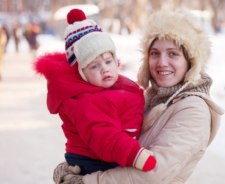 Portrait of happy mother with toddler  in winter