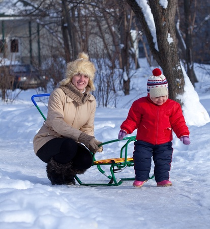 Happy mother with toddler   in winter day photo