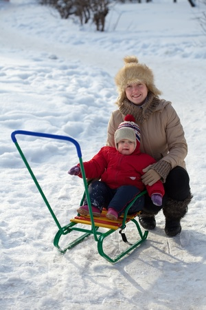 Happy mother with toddler on sled  in winter photo
