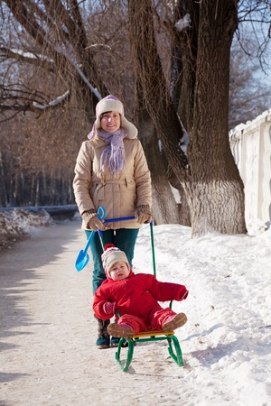 Happy mother with toddler on sled  in winter Stock Photo - 13550201