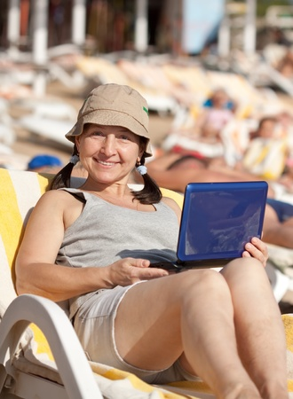 Happy mature woman sitting  with laptop at resort beach Stock Photo - 13550345