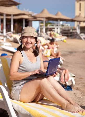 Happy mature woman sitting  with laptop at resort beach Stock Photo - 13550252