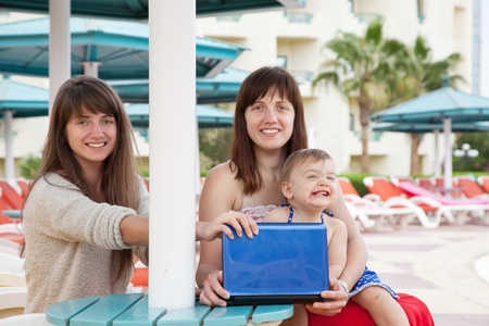 happy girls   sitting  with laptop at resort beach photo