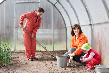 Happy women with child works at hothouse in spring photo