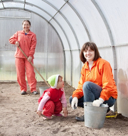 Happy women with child works at hothouse in spring Stock Photo - 13550346
