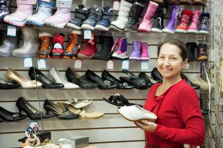 Mature woman chooses shoes at fashionable shop photo