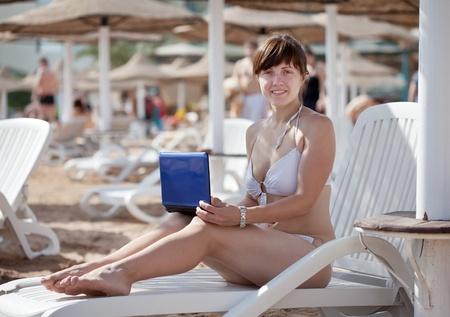 Happy  woman using  laptop at resort beach photo