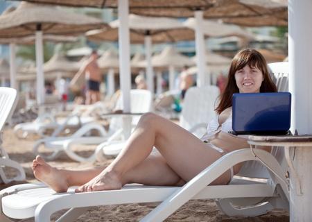 Happy  woman using  laptop at resort beach Stock Photo - 13570238