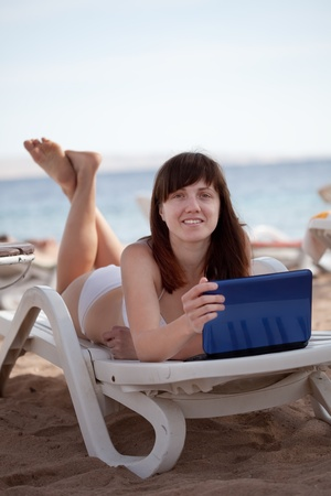 Happy  woman  with laptop at resort beach photo