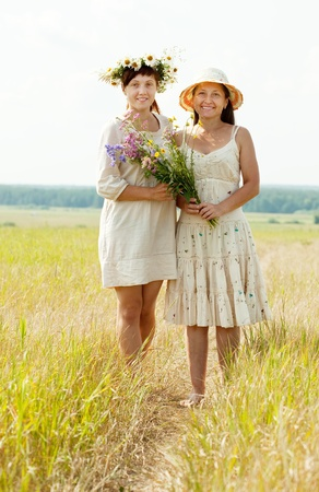 Portrait of two happy women with flowers in summer field photo