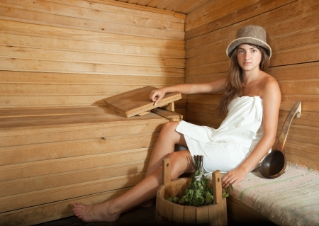 stive: girl sitting on wooden bench in sauna