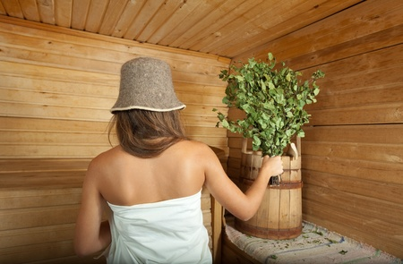 bathhouse: girl is steamed in the sauna with birch flag broom