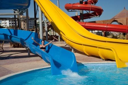 aqua park: Young beautiful caucasian woman in bikini on swimming pool water slide