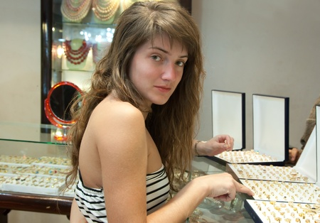 woman  chooses jewelry at   shop photo